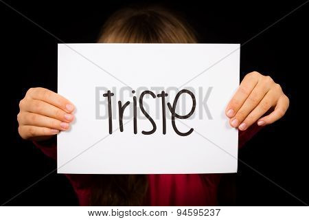 Child Holding Sign With Spanish Word Triste - Sorry