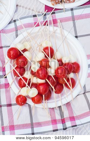 Red cherry tomatoes with mozzarella on shpashkah as a snack at the picnic