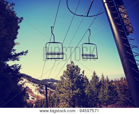 Empty chairlift in ski resort. Shot in summer with green grass and very little snow toned with a retro vintage instagram filter