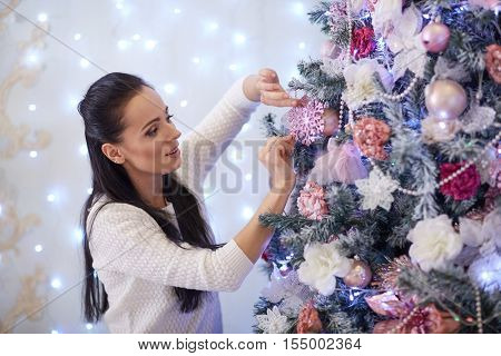 Beautiful young woman is decorating a Christmas tree in the house. Merry Christmas and New Year.