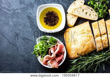 Bread ciabatta, jamon ham serrano paleta iberica, arugula, olive pepper oil, rosemary and glass of red wine on stone slate black background. Top view copy space