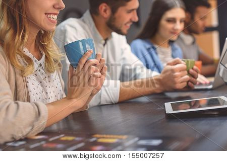 We are all good friends. Close up shot of attractive young girl holding cup with drink and sitting in cafe with her friends