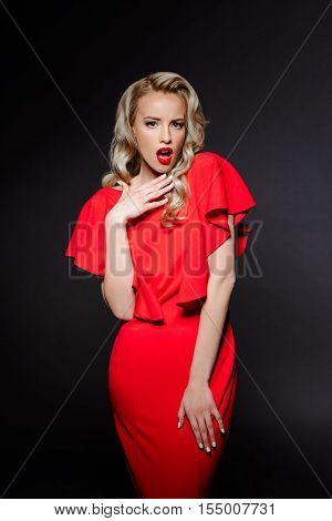 Surprised young beautiful blonde girl in red evening dress looking at camera at party over grey background. Copy space.