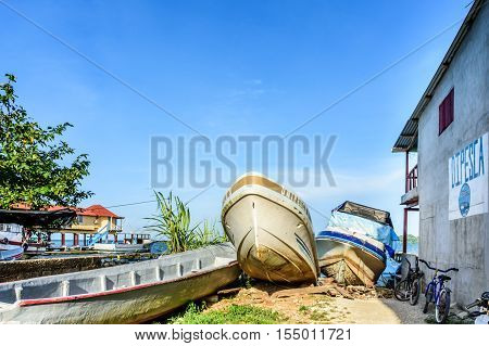 Livingston, Guatemala - August 31 2016: Late afternoon sun lights fishing boats pulled ashore on riverbank of Rio Dulce in Caribbean town of Livingston