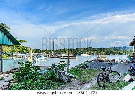 Livingston, Guatemala - August 31 2016: Late afternoon sun lights anchored fishing boats & workers in commercial dock area in Caribbean town of Livingston on Rio Dulce