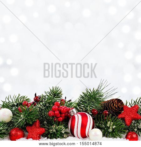 Red And White Christmas Ornaments And Branches In Snow With Twinkling Silver Background