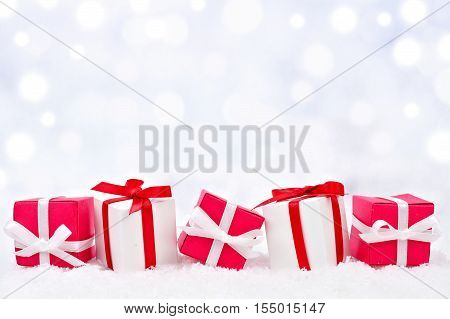 Red And White Christmas Gifts In Snow With Twinkling Silver Background