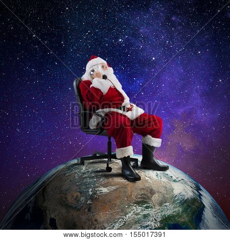 Santa Claus receives requests via telephone sitting in a chair on a big world