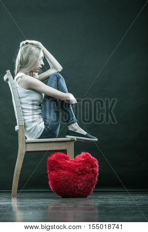 Broken heart love concept. Sad unhappy woman sitting on chair red heart pillow on floor dark background