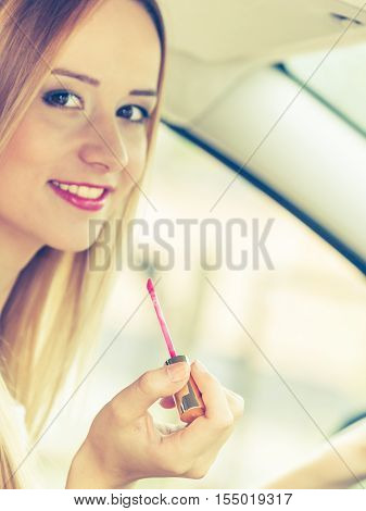 Distracted driver. Young attractive woman painting her lips doing applying make up while driving the car.