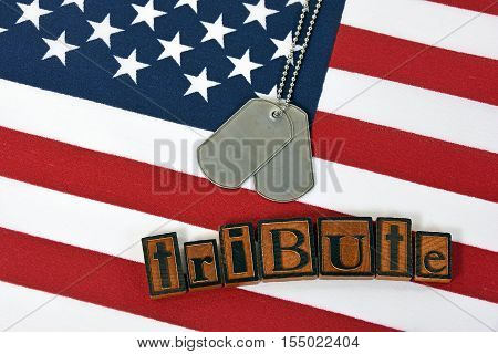 military dog tags and word tribute in wooden letterpress type on American flag