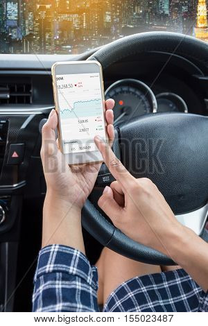 Business woman driver a touch screen of white smartphone check stock market or exchange and hand holding steering wheel in a car with night city background
