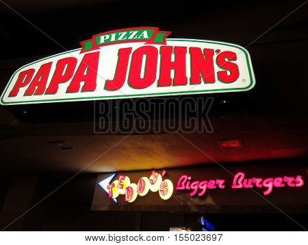 HONOLULU OAHU - JUNE 8: Papa John's Pizza and Teddy's Bigger Burger signs at Night taken June 8 2016 Honolulu Hawaii.