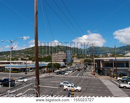 HONOLULU - MARCH 19: University townscape featuring street with cars people retail shops and Mountains with homes in the background in Honolulu Hawaii. Taken on March 19 2014