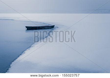 Alone Boat On Frozen Lake In Winter