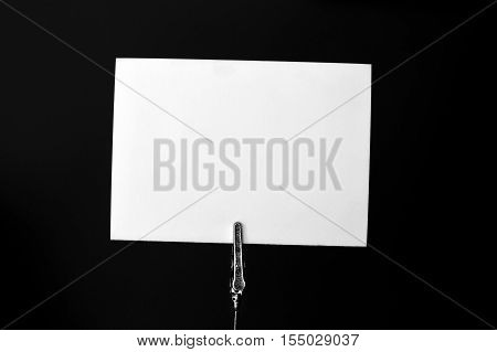 White Blank card on metallic holder ready for text on black background