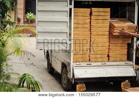 A courier man loading materials in a small truck to dispatch the shipment. The face of the worker are not visible and the photograph is taken from the back of the workers.