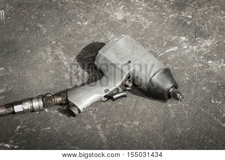 Old used pneumatic impact wrench on concrete floor in the sun with vintage effect