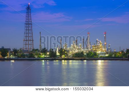 Oil refinery river front at twilight, industrial manufacturing background