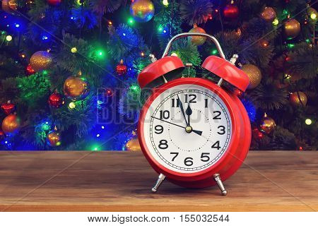 Red retro alarm clock at twelve o'clock on blurred Christmas background with bokeh. Midnight. Minutes about New year.
