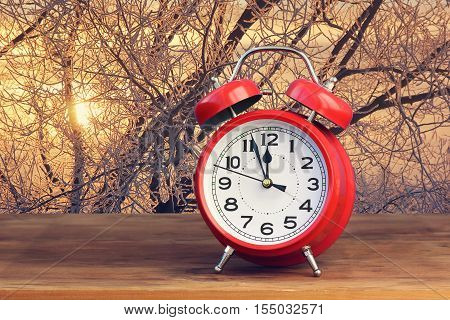 Red retro alarm clock at twelve o'clock on the backdrop of a winter sunset. Midnight midday. Minutes about New year.
