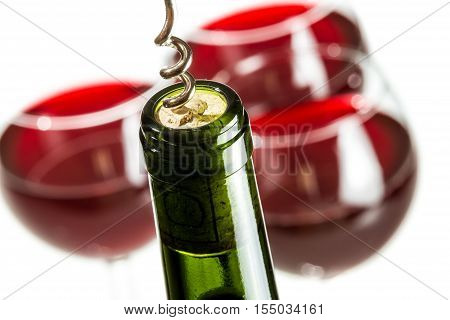 Closeup of opening green wine bottle on white background