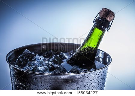 Ice Bucket with ice and champagne on blue background