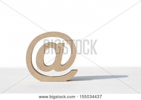 Wooden email symbol on white table, white background