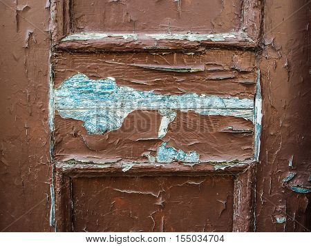 A very worn and battered old brown door