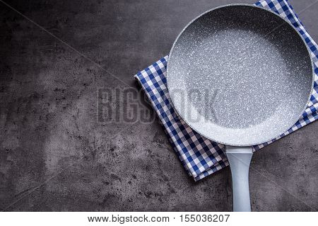 Ceramic pan on concrete kitchen board. Kitchen utensil. Empty pan.