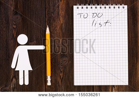 Paper woman holding pencil and blank notebook with todo list wooden background. Abstract conceptual image