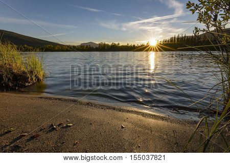 Last sunbeams during tranquil sunset over calm lake, Sweden poster