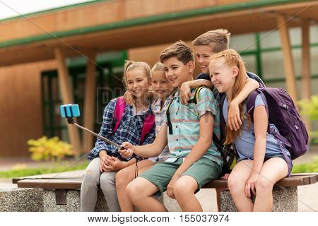 primary education, technology, friendship, childhood and people concept - group of elementary school students with backpacks sitting on bench taking picture by smartphone on selfie stick outdoors