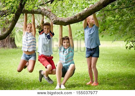 friendship, childhood, leisure and people concept - group of happy kids or friends hanging on tree and having fun in summer park