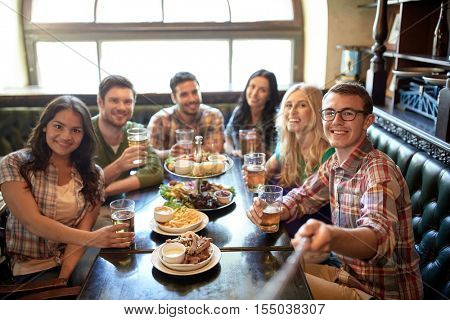 people, leisure, friendship and technology concept - happy friends taking picture by selfie stick, drinking beer and eating snacks at bar or pub