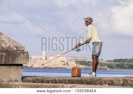Havana, Cuba on December 22, 2016: Fisherman with rod on Malecon in front of Castillo de los Tres Reyes del Morro