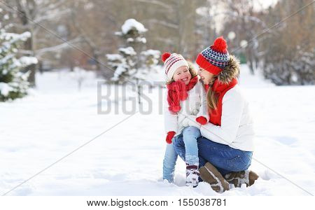 happy family mother and child daughter having fun playing at winter walk outdoors