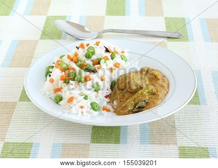 Indian food rice pilaf, which is a popular and traditional dish, and side dish curry made from long green pepper or chili.