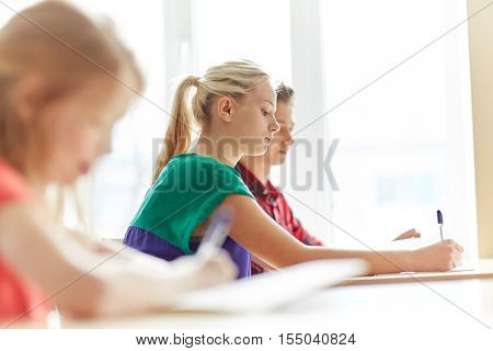 education, learning and people concept - group of students with books writing school test