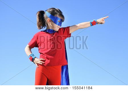 Superhero Girl Points Towards Dramatic Blue Sky