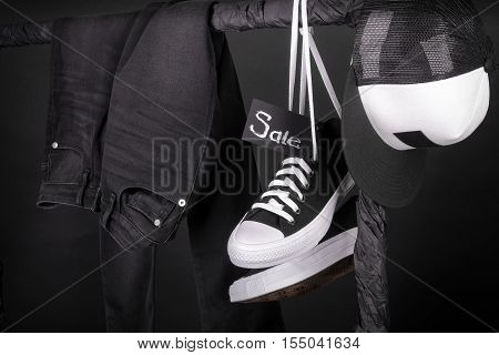Sale Sign. Black Friday.  And White Sneakers, Cap  Pant, Jeans Hanging On Clothes Rack   Background.