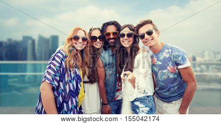 summer vacation, travel, tourism, technology and people concept - smiling young hippie friends taking picture by smartphone selfie stick over singapore city background