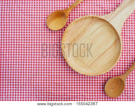 Empty plate and spoons on red checked tablecloth. Top view.with handle