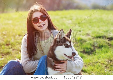 Young Girl Sitting In Park With Brown Husky Puppy