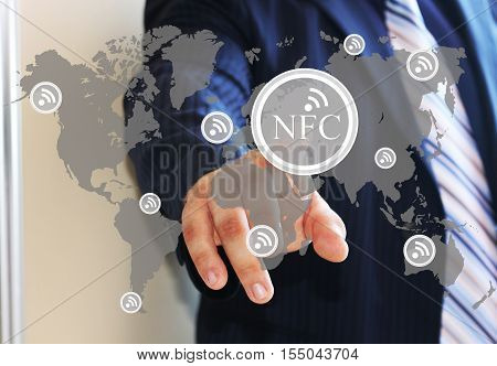 The businessman clicks on the NFC icon on the world map. NFC near field communication network. Web icons.The latest technology. The web icons.