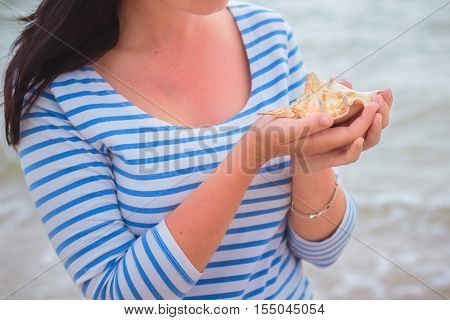 Young beautiful slim girl with brown hair standing on a seashore one windy morning and holding a seashell.