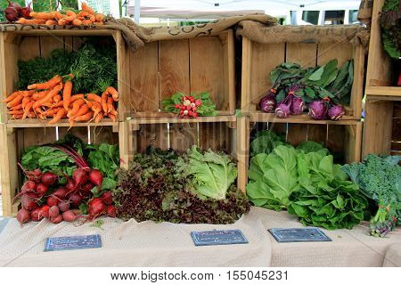 Wood crates laying on side, with wonderful display of fresh-picked vegetables at farmers market.