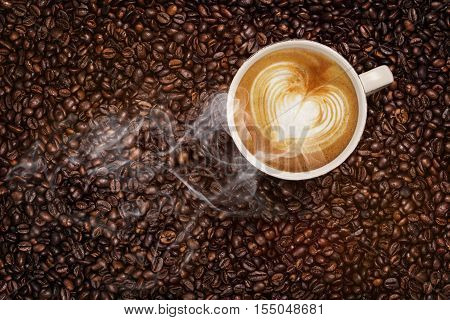 Steaming Cup Of Coffee On Coffee Beans