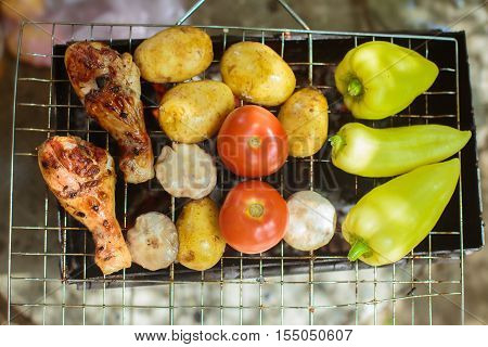 Barbecue. B-B-Q. Grille chicken meat and vegetables on the grill. Summer rest. A man preparing chicken meat and vegetables on the grill