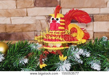 Cash Cockerel - the symbol of the New year sitting on fir branches on the background of brick wall